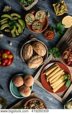 high angle view of some different vegan side dishes and dips such as guacamole or sweet potato sobrasada, and some other ingredients to prepare vegan appetizers, on a gray rustic wooden table
