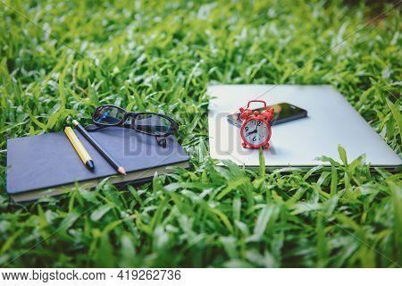 Computer Laptop And Personal Accessories Device On Grass Fields, Business Outdoors Space Of Freelanc