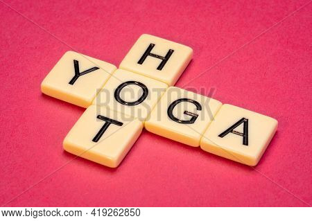 hot yoga crossword in ivory letter tiles against textured paper, form of yoga as exercise performed under hot and humid conditions