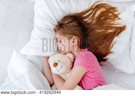 Little beautiful girl lying in the bed hugging teddy bear and sleeping. Preteen child resting wearing pink t-shirt and holding toy. Portrait of pretty female kid with long hair