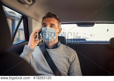 Mature business man wearing a face mask for safety against covid-19 sitting in car rear seat and talking over phone. Man in a business call in taxi ride wearing face mask for precaution against corona