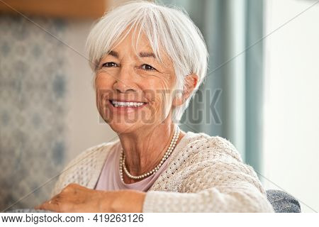 Happy old woman with white hair sitting on sofa and looking at camera. Retired woman relaxing on her couch in the living room. Close up face of cheerful senior lady with big grin enjoying retirement.
