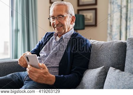 Smiling old man using smartphone while sitting on couch. Happy elderly man with spectacles messaging on mobile phone at home. Senior in video call with his family on smart phone at nursing home.