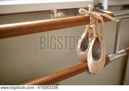 Pink ballet shoe hanging on barre, nobody