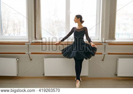 Ballerina doing exercise at barre in class
