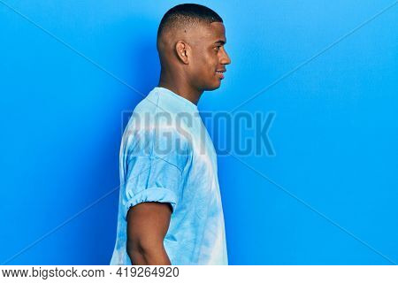 Young black man wearing tye die t shirt looking to side, relax profile pose with natural face with confident smile.