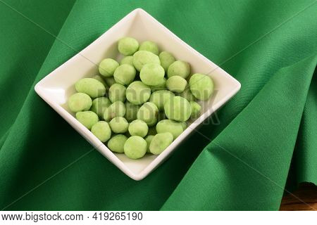 Wasabi Covered And Flavored Peanuts In White Snack Bowl On Green Fabric