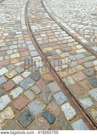 Old Tram Rails On Paving Stones Converging Towards The Horizon, Selective Focus