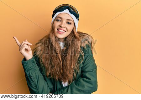 Beautiful blonde caucasian woman wearing snow wear and sky glasses smiling happy pointing with hand and finger to the side