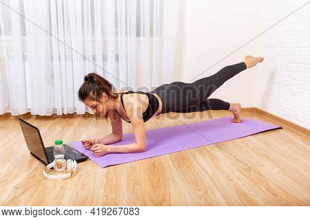 Fit Woman Doing Yoga Plank And Watching Online Tutorials On Laptop, Training In Living Room. Woman W