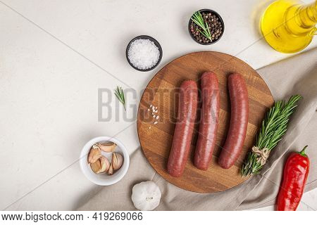 Raw Meat Beef Sausages For Grill And Spicy, Herbs Rosemary, Pepper, Salt On Table. Food Background F