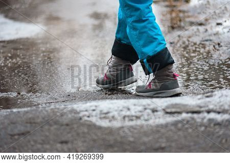 Person In Waterproof Boots Standing On Dirty Melting Snow Slush