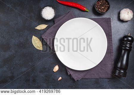Epmty Plate On Black Stone Background And Spice, Pepper, Salt. Cooking Food Background For Menu In R