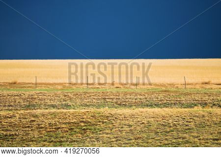 Rustic Fence On Vast Grasslands For Livestock Surrounded By Thunderstorms In The Distance Taken On A