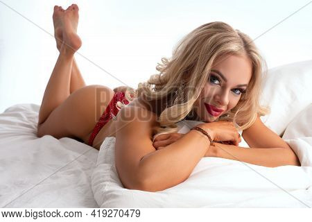 Blond Muscular Woman In Bikini Lying On Bed Looking At Camera