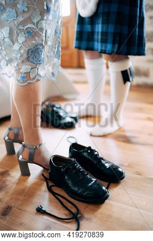 Preparing For A Scottish Wedding. Man In A Kilt And Sporran Stands Next To Woman In A Skirt And High