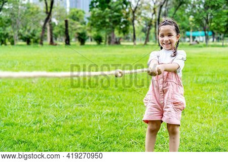 Cheerful Child Girl Having Fun To Playing Tug Of War At The Park, Smiling Girl Pulling A Rope On The