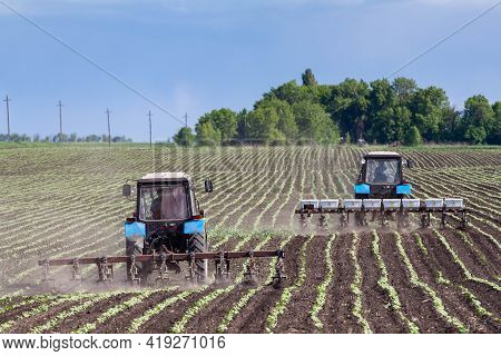 Field Work In Agriculture. Farmers Tractor Harrows The Field After Planting Seeds. Tractor And Seede