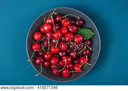 Cherry With Leaf Water Drops On Bowl On Blue Background. Ripe Ripe Cherries. Sweet Red Cherries. Top