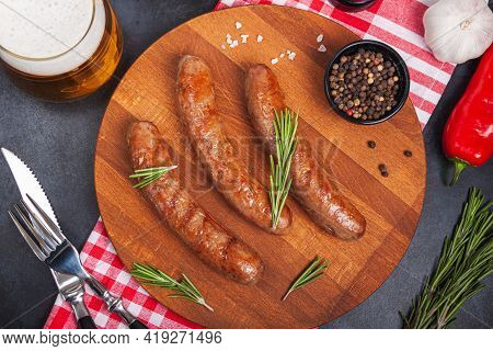 Grilled Meat Beef Sausages With Rosemary Herb On Wooden Cutting Board On Black Table. Food Backgroun