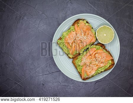 Tasty Sandwich With Dark Rye Bread, Avocado And Salmon. Homemade Toast On Gray Concrete Background.