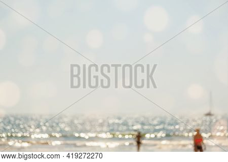 Abstract Seascape Blurred Beach Background With People. Blur Bokeh Light Of Calm Sea And Sky. Summer