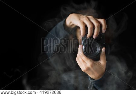 Womans Hands Held Photo Camera. Close Up Shot. A Person In Black Hoodie And Smoke Around