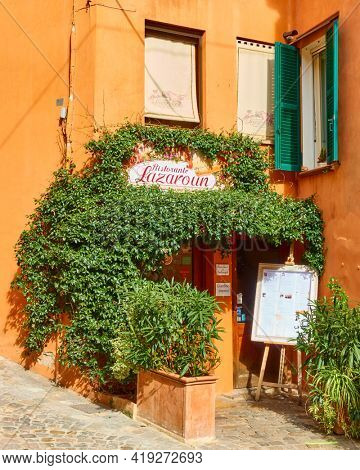 Santarcangelo di Romagna,  Italy - February 26, 2020:  Small cosy italian restaurant with ivied entrance in Santarcangelo di Romagna town in Rimini province.