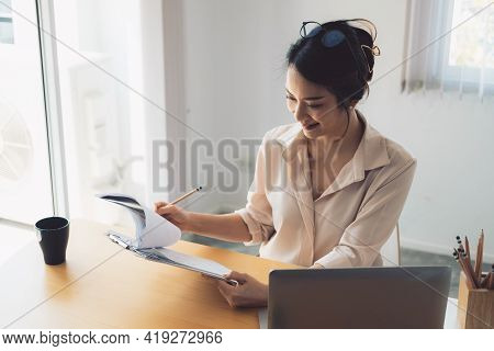 Female Asian Businesswoman Analyzing The Business Report With Laptop Computer In The Office.