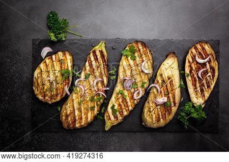 Grilled Eggplant Slices, Garnished With Fresh Herbs, On Black Background, Top View