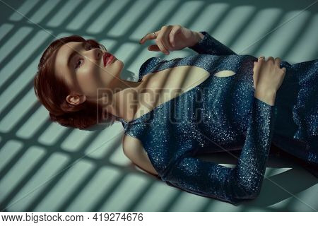 Beautiful girl in evening dress lies on the floor in the shade of sunset. Hair and makeup in the style of the 20s. Art fashion.