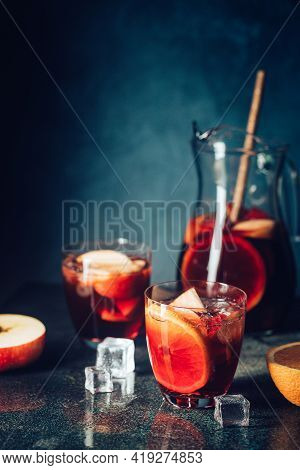 Refreshing Red Wine Sangria Or Punch With Fresh Fruits In Glasses And Pincher On Black Background
