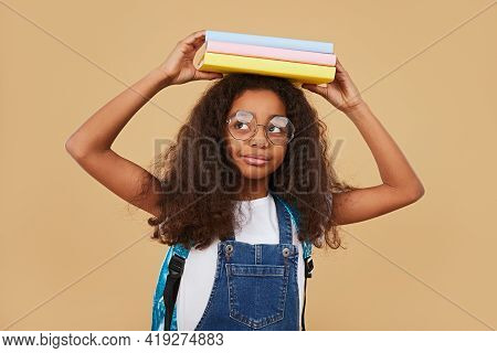 Clever African American Schoolgirl With Curly Hair Wearing Denim Overall And Glasses Carrying Stack