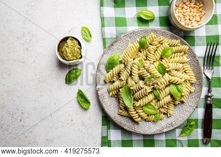 Italian Fussili Pasta With Basil Pesto And Fresh Basil On White Stone Background. Top View.