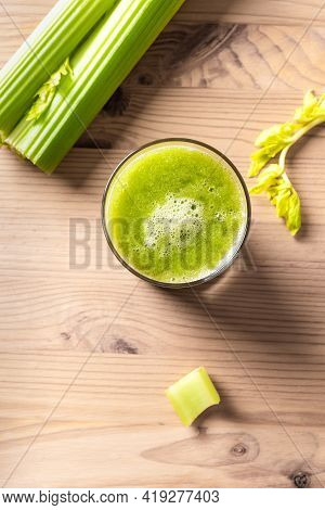 Celery Juice In Glasses. Fresh Squeezed Detox Green Juice And Bunch Of Organic Celery On Wooden Tabl