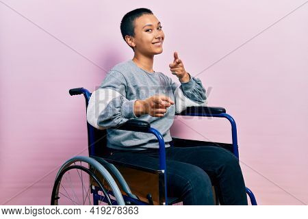 Beautiful hispanic woman with short hair sitting on wheelchair pointing fingers to camera with happy and funny face. good energy and vibes.