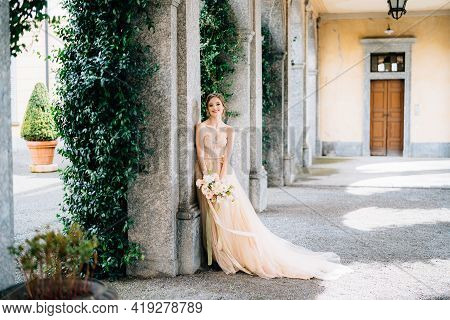 Smiling Bride In A Dress With A Bouquet Of Pink Flowers Leaning Against A Pillar In A Vaulted Room.