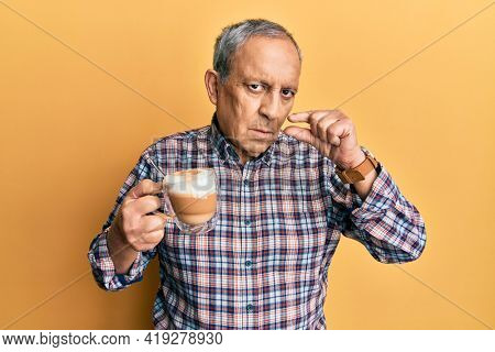 Handsome senior man with grey hair drinking a cup coffee mouth and lips shut as zip with fingers. secret and silent, taboo talking