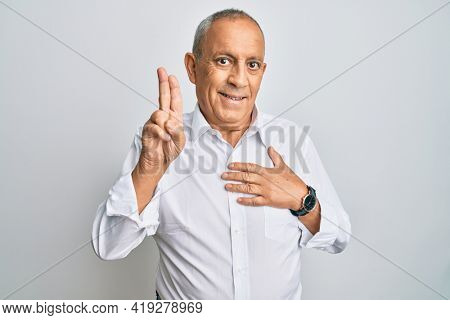 Handsome senior man wearing casual white shirt smiling swearing with hand on chest and fingers up, making a loyalty promise oath
