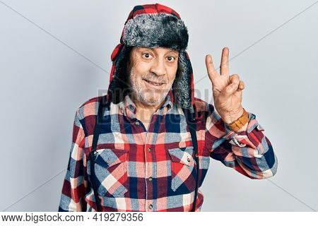 Handsome mature man wearing winter hat with ear flaps smiling with happy face winking at the camera doing victory sign. number two.