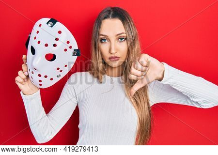 Young blonde girl holding hockey mask with angry face, negative sign showing dislike with thumbs down, rejection concept