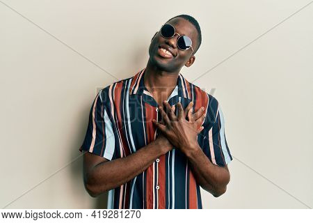 Young african american man wearing casual clothes and sunglasses smiling with hands on chest, eyes closed with grateful gesture on face. health concept.