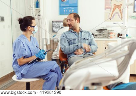 Orthodontist Nurse Discussing With Man Patient About Tooth Consultation