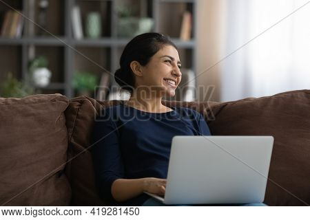 Excited Dreamy Indian Woman Distracted From Laptop, Sitting On Couch