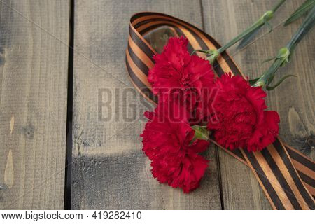 Bouquet Of Red Carnations With A St. George Ribbon On A Wooden Background. Georgievsk Ribbon - Russi