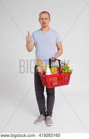 Full Length Portrait Of Young Man With Shopping Basket Full Of Products Thumbs Up Over White Backgro