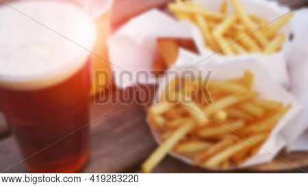 Blurred Abstract Background. Dark Beer And Fries On A Wooden Table. Food Court. Takeaway Food, Food