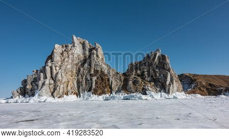A Picturesque Two-headed Rock, Devoid Of Vegetation, Rises Above The Frozen Lake. Cracks On The Shee
