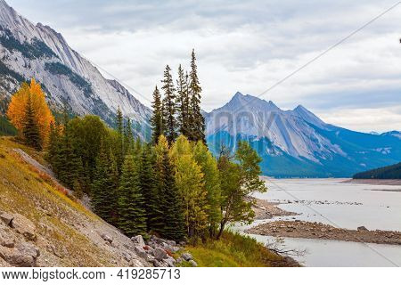 The Canadian Rockies. The shallow Medicine lake is fed by melted glacial waters. The lake is surrounded by mountain peaks. Cloudy autumn day