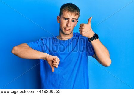 Young caucasian man wearing casual blue t shirt doing thumbs up and down, disagreement and agreement expression. crazy conflict
